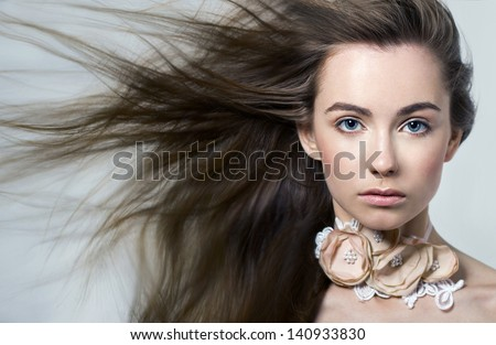 Developing hair.Hair. Beauty.Air.Female portrait . White. Background. Close-up. Space. Natural make-up.Grey. Necklace.Earring.Eyebrows.Full lips.Girl .Woman. hair motion on white background isolated  - stock photo