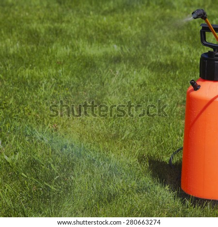 Device of spraying pesticide at the sunshine produces a rainbow over green grass. - stock photo
