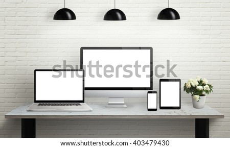 Devices on desk with isolated screen for mockup. Computer display, laptop, tablet and smart phone on office desk. Flowers, lamps and brick wall in background. - stock photo