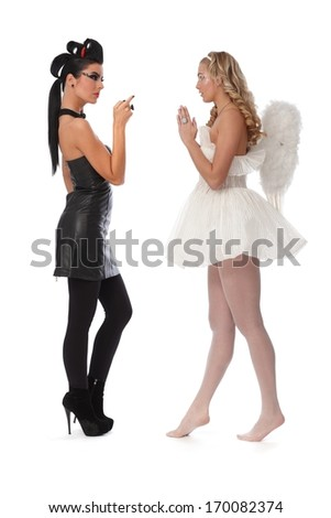 Devil looking angry, angel praying, side view, full-length. - stock photo