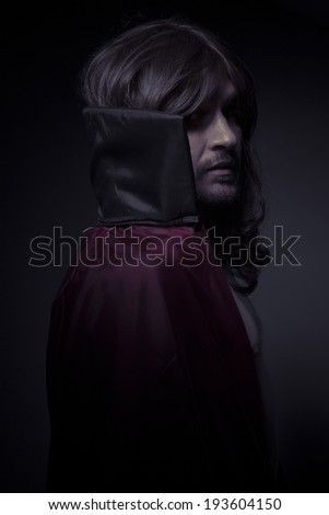 Devil man with long hair and black coat - stock photo