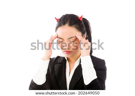 Devil side of a young Asian businesswoman suffering with headache isolated on white background