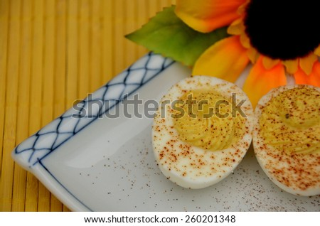 Deviled eggs sprinkled with paprika, served on decorative plate. Perfect appetizer for family and friends. Serve everyday or for special occasions, including parties, celebrations or holidays. - stock photo