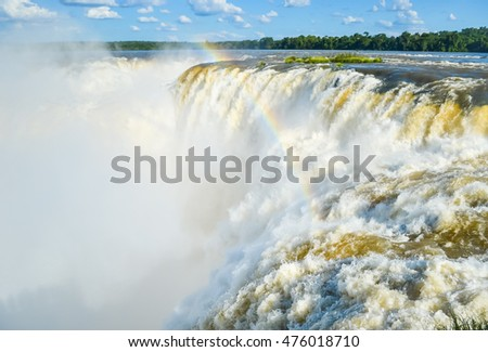 Devils throat of Iguazu waterfall with strong flow and water spray with soft focus in Brazil