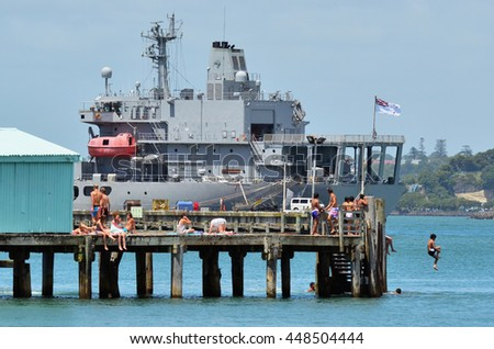 DEVONPORT, NZ - JAN 31 2012:New Zealand youth sunbath and jump from Devonport pier. Devonport hosts the Naval Base of the Royal NZ Navy but is best known for its charming lifestyle.