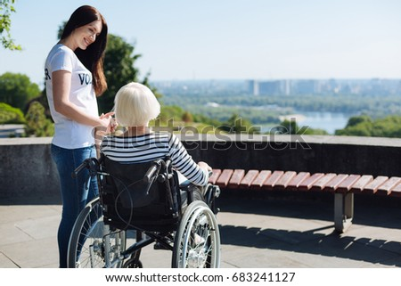 Devoted bright girl holding elderly lady by the hand