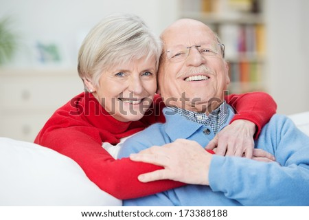 Devoted happy senior couple sitting in a close embrace on a sofa in the living room relaxing and laughing - stock photo