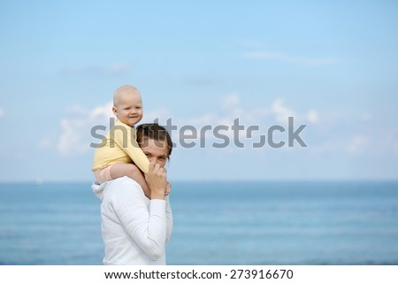 Devoted mother and adorable smiling child cuddling, spending bonding quality time on beach with blue waters in the background. Attentive parenting and family lifestyle concept.  - stock photo