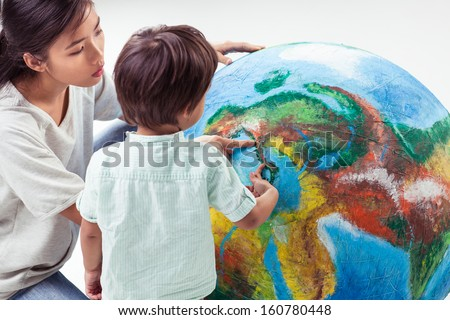 Devoted mother teaching her son about our planet using a model of planet Earth.