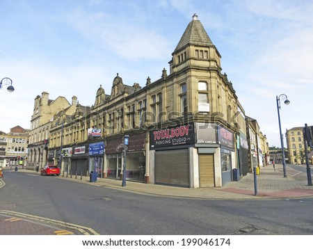 DEWSBURY, UK -JUNE 16: Shops, Dewsbury, West Yorkshire, England, UK, 16 June 2014. Dewsbury,  after a period of decline, is redeveloping  derelict mills into flats and regenerating city areas. - stock photo