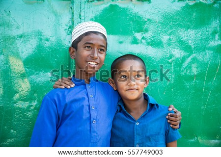 DHAKA, BANGLADESH - JANUARY 8, 2017: Two arabic muslim friends are holding eachother at the shoulders against a green background