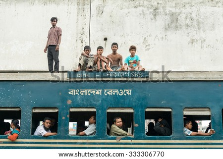 Dhaka, Bangladesh - July 19, 2014: Commuters in train looking through window. Trains are very cheap and poorly maintained but it's the best option to witness a bit of everyday local life. - stock photo
