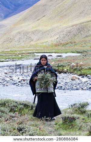 DHO TARAP, DOLPO, NEPAL - SEPTEMBER 11: Beautiful Tibetan woman in national clothes waiting for Puja ceremony during Full Moon Festival on September 11, 2011 in Dho Tarap village, Nepal - stock photo