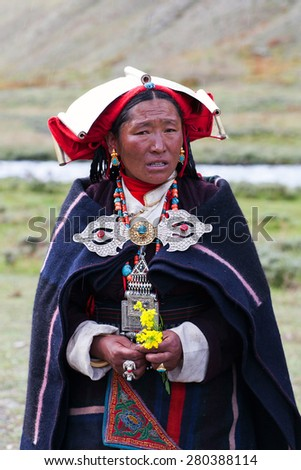 DHO TARAP, DOLPO, NEPAL - SEPTEMBER 11: Tibetan woman in national clothes poses for a photo during Dho Tarap Full Moon Festival on September 11, 2011 in Dho Tarap village, Dolpo district, Nepal