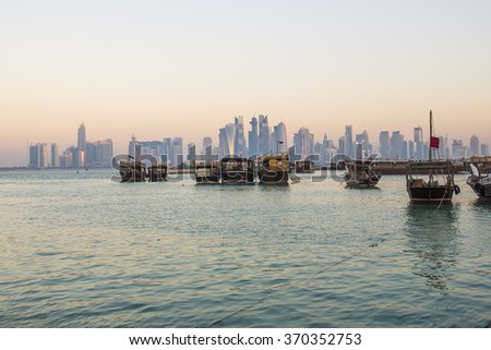 Dhows moored off at the corniche in central Doha, Qatar, Arabia, with some of the buildings from the city's commercial port in the background.