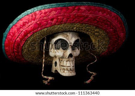 Dia De Los Muertos (Day of the Dead) skull wearing colorful Mexican sombrero on isolated on black background - stock photo