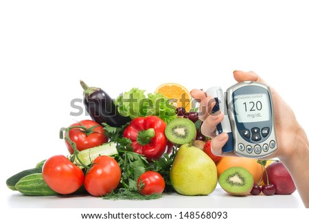 Diabetes concept glucose meter in hand and healthy organic food fruits and vegetables green apple, orange, tomatoes, cucumbers, parsley, kiwi, grapefruit, salad, peach, cherries on a white background