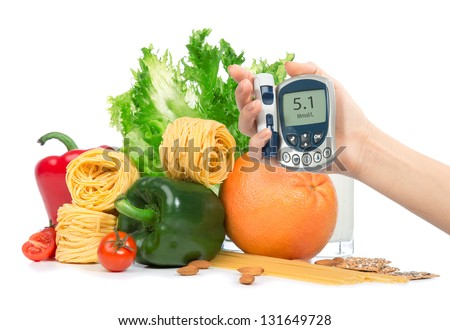 Diabetes concept glucose meter in hand and healthy organic green and red pepper, tomatoes, almonds, fresh salad, spaghetti, grapefruit, glass of milk on a white background - stock photo