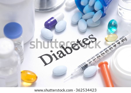 Diabetes concept with insulin, syringe, vials, pills, and stethoscope.