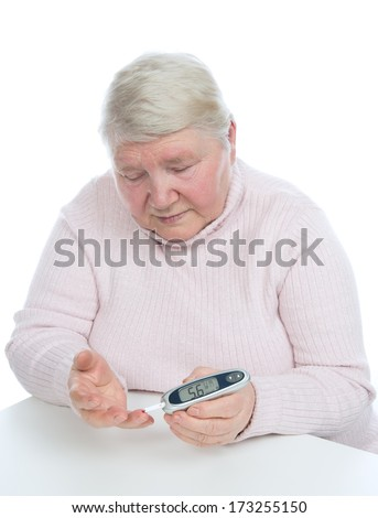 Diabetes patient senior woman measuring glucose level blood test with glucometer and small drop of blood on a white background - stock photo