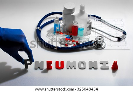 Diagnosis - Pneumonia. Medical concept with pills, injection, stethoscope, cardiogram and a syringe - stock photo