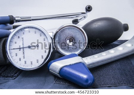 Diagnostic set or kit that includes stethoscope sphygmomanometer (blood pressure gauge) with bulb and neurological reflex hammer lying on the cuff. Tools for doctor neurologist or general practitioner - stock photo