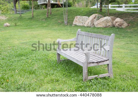 diagonal wooden bench in green garden lawn for resting and relax - stock photo