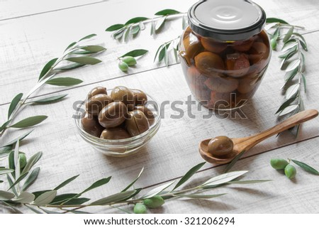 Diagonally of horizontal frame in row glass bowl of green olives and jar of olives framed by olive tree branches, spoon with olive on wooden white background. Green olives in the bowl and jar.  - stock photo