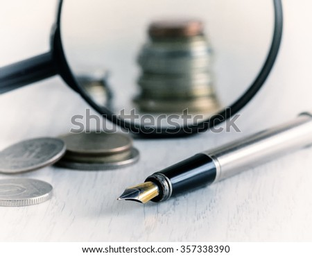 diagram of the coins, pens and a magnifying glass on a light background, close-up, vintage - stock photo