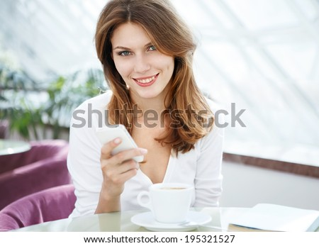 Dial a phone number / photo of beautiful woman sitting in a coffee house