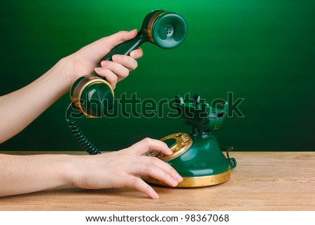Dialing on retro phone on wooden table on green background - stock photo