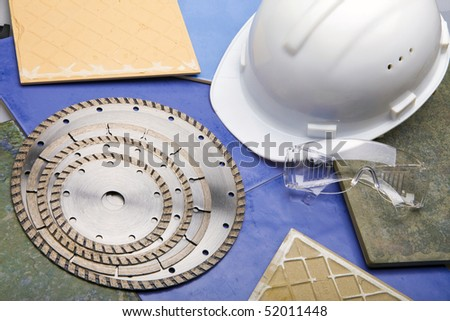 Diamond discs for cutting of tile, building goggles and helmet - stock photo