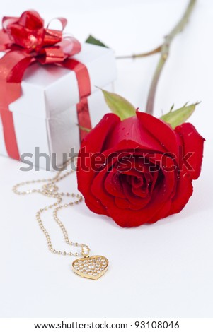 Diamond heart shape pendant and red rose - stock photo