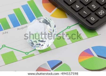 Diamond on a table with business charts and a calculator wealth management concept
