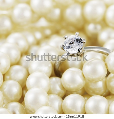 diamond ring and pearl necklace - stock photo