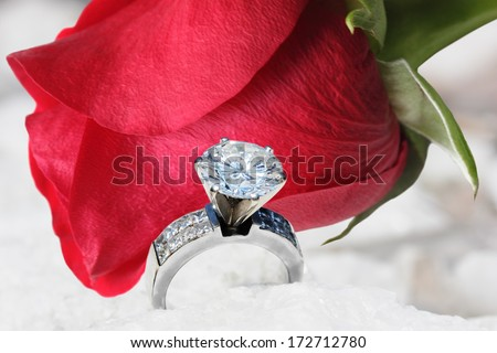 Diamond Ring and red rose on snow background - stock photo