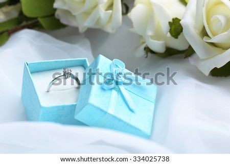 Diamond ring in box on a white cloth - stock photo