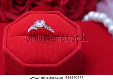 diamond ring in red box with flowers - stock photo