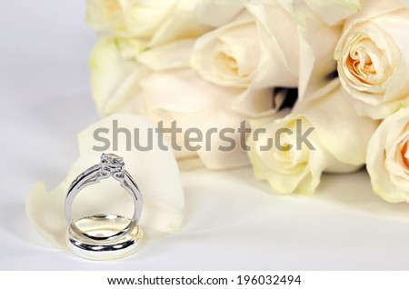 diamond ring on a white rose petal with bridal rose bridal bouquet