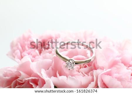 Diamond ring on pink marzipan flower - stock photo