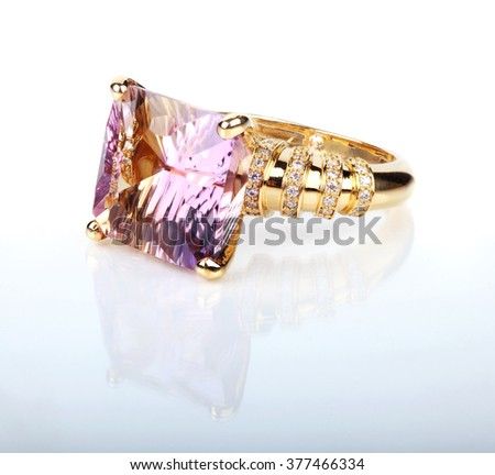 diamond ring with purple gemstone closeup shot on white background - stock photo
