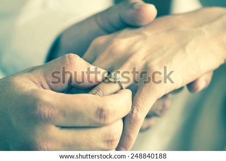 Diamond wedding ring,groom and bride hand in wedding ceremony - stock photo