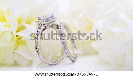 Diamond white gold ring. White Flower background - stock photo