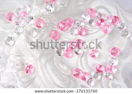 diamonds on white floral fabric - stock photo