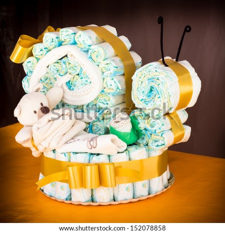 Diapers rolled up to create a diaper snail cake with baby clothes and ribbon - stock photo