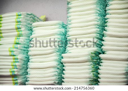 Diapers stacked in a piles in the child room. - stock photo