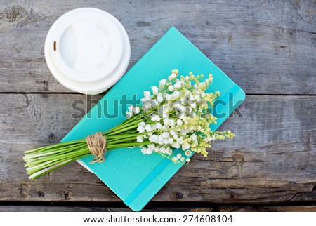 diary, a glass of coffee and  lilies of valley  on the table - stock photo