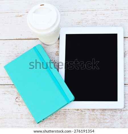 diary, a tablet computer, a glass of coffee on the table - stock photo