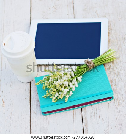 diary, a tablet computerand  lilies of valley on the table - stock photo