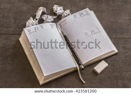 Diary and pen lie beside crumpled pieces of paper on dark background